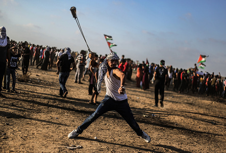 A Palestinian demonstrator throws stones using a slingshot during an anti-Israel demonstration at the Israel-Gaza border fence in the southern Gaza Strip.