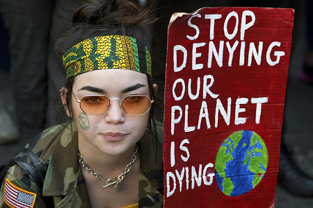 Environmental activist seen holding a placard outside the Brazilian embassy in London.
