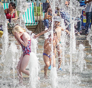 Kids plays in fountains at the Peace Gardens during a warm Sunday. Meteorologists forecast the temperatures at 30 degrees Celsius in many parts in the UK over the Bank Holidays.