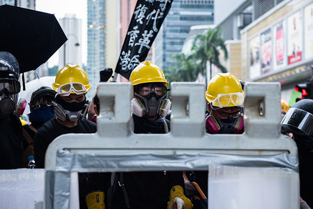 Protesters gaze at riot police from behind a barricade during the demonstration. Thousands of protesters again took the streets to oppose the controversial extradition bill. What started as a peaceful march ended in violence as police fired dozens of rounds of tear gas and various projectiles, while protesters hurled bricks and molotov cocktails.