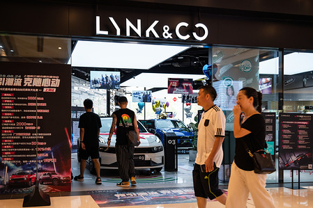 Pedestrians walk past a Chinese-Swedish automotive brand Lynk & Co store in Shanghai.