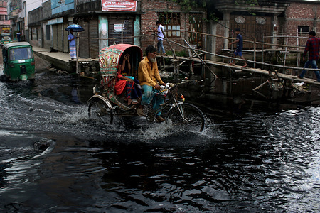 A rickshaw goes over dyed and polluted water that is being released into a canal that leads to the Buriganga river in Dhaka. Some canals in Dhaka city are completely filled up by dumping garbage and may not be recovered anymore and rest of the other canals and river contain pitch black water with noxious fume.