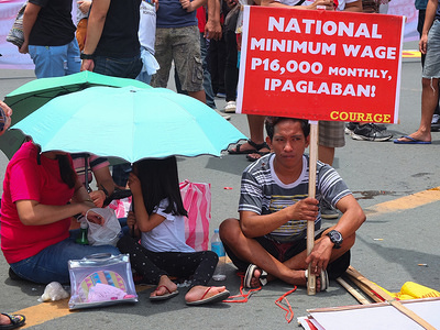 """A man holds a placard next to his family on the street, during the demonstration. Thousands of workers took to the streets as the Philippines marked National Heroes' Day. They call it the """"Martsa ng Manggagawa Laban sa Kontraktwalisasyon"""" (Workers' March Against Contractualization). They slammed the Duterte Government for allegedly turning a blind eye to the abuses suffered by workers. The United workers calling for an end to """"ENDO"""" or end of contractualization of workers and the increase of minimum wage of workers to 750 pesos."""