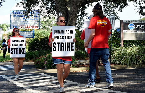 Union members hold placards in front of an AT&T office as a strike by the Communication Workers of America enters its fifth day across nine Southern states. More than 20,000 CWA union members walked out after charging that the telecommunications company isn't bargaining in good faith over a new contract.