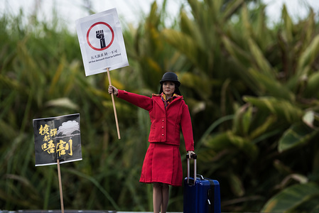 A miniature figure of an aviation worker holds a placard during the demonstration. Anti-government protesters rallied in support of aviation workers that had been let go due to their political views and participation in various anti-extradition demonstrations. Various leaders gave speeches before the demonstrators marched to Pacific Place and created a 'Lennon Wall'.