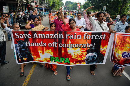Protesters chant slogans while holding a banner during the protest against the devastating wild fire in amazon and highlighting qualms about the controlling policies taken up by the Brazilian President Jair Messias Bolsonaro. The raging fires burning down massive stretches of Amazon rain-forest, have intensified through August 2019 threatening the life of multitudes. Among the 80000 fires so far this year, this is recorded to be the deadliest by the country's National Institute for Space Research (INPE).
