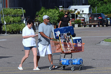 People push a shopping cart of hurricane supplies to their car in a Home Depot parking lot in preparation for the arrival of Hurricane Dorian which is expected to become a Category 4 hurricane before making landfall in Florida on Labor Day.