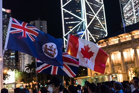 Protesters wave various flags of nations with a history of British colonisation during the commemoration Protesters gathered to commemorate the 74th anniversary of the liberation of Hong Kong and reaffirm their support of the anti-extradition movement. Protesters stood in silence with flowers and signs before chanting various anti-extradition slogans.