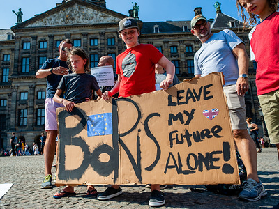 Two boys hold a placard against Primer Minister Boris during the protest. This Saturday a wave of protests are taking place against British Prime Minister Boris Johnson and after his request to suspend UK Parliament from mid-September was approved by Queen Elizabeth. In Amsterdam, a group of English people gathered at the Dam square to show their solidarity from abroad, defend democracy and fight against Boris Johnson's coup.