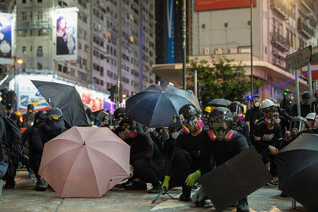Protesters occupy a road during the demonstration. Unrest in Hong Kong continues as thousands of protesters took part in a illegal anti government demonstration. Petrol bombs has been thrown by the protesters and the police fired multiple rounds of rubber bullets towards the protesters.