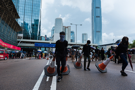 Protesters drag traffic cones to be used as makeshift barricades during the demonstration. Against police orders, thousands of anti-government protesters marched through streets. Clashes with police resulted in dozens of tear gas rounds and projectiles being fired, eventually leading to multiple arrests. Despite continued pressure by protesters, the Hong Kong government has yet to cave to the protesters demand of fully withdrawing the extradition bill.