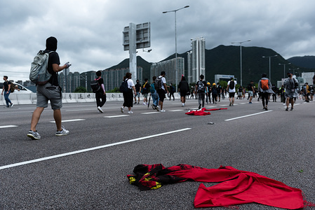 A burned and tattered Chinese flag lies on the ground as protesters walk away from the airport during the demonstration. Anti-government protesters occupied roads leading toward Hong Kong International Airport in support of the anti-extradition movement. Protesters used barricades the block highways, forcing airport staff and passengers to walk along the road to reach the airport. So far, the government has yet to yield to any of the protesters' 5 demands, including the full withdrawal of the extradition bill.