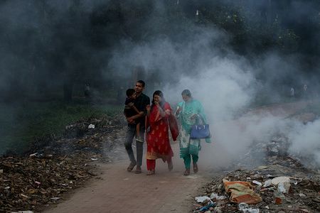People walk as the garbage burns beside a street at a park in Dhaka. Dhaka was named the second most polluted capital city in the world in 2018, according to a study by IQ Air Visuals, a Swiss based group that gather air quality data globally. The situation is very serious, as the expert says. The five of the top 10 causes of death in Bangladesh related to air pollution.