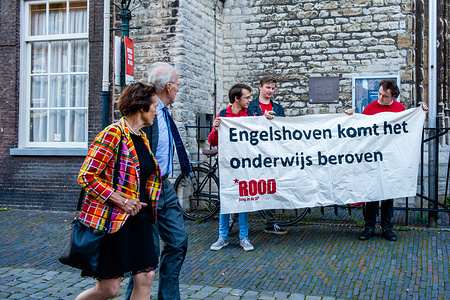 People hold a protest banner outside the entrance to the official ceremony. As the Executive Board of Leiden University attended the opening of the academic year 2019-2020, hundreds of students gathered to protest against the cutbacks in university education in The Netherlands suggested by the Van Rijn committee's advice report on the funding of higher education. The protest took place close to the official ceremony at the Pieterskerk church and speakers from all over the scientific field were involved.
