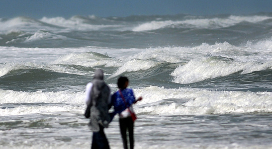 A couple walk on the shore of the beach as they enjoy heavy surf from Hurricane Dorian. The category 5 storm is slowly moving toward the coast of Florida after hammering the Bahamas and gradually losing strength.