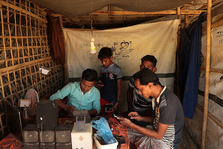 A Rohingya refugee repairs mobile phones and other electronic items at a roadside makeshift tent in a refugee camp in Bangladesh's Cox's Bazar district.