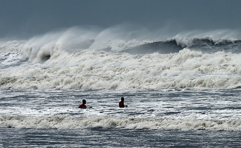 Two men enjoy the heavy waves as Hurricane Dorian turns to the north off the eastern coast of Florida after a weakened Category 2 storm  devastates parts of the Bahamas.