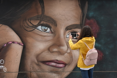 A woman takes a photo of a street art in Lima, Peru.