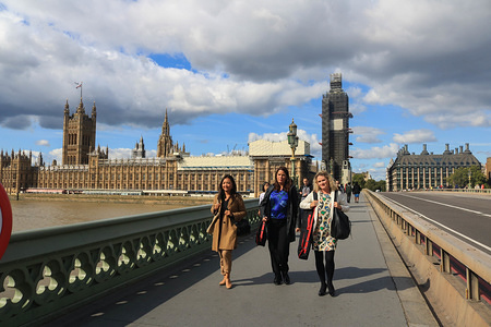 Pedestrians walk on Westminster Bridge during a day of sunny spells in London.