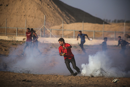 Demonstrators flee from tear gas canisters fired towards them during an anti-Israel demonstration at the Israel-Gaza border fence in the southern Gaza Strip.