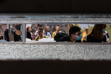 Protesters peek into the station entrance to survey the damage during the demonstration. Anti-government protesters took to the streets again in the latest round of anti-extradition demonstrations. Protesters targeted the area around which the August 31st MTR incident occurred, vandalizing various MTR station entrances. Riot police eventually arrived and conducted a dispersal operation.