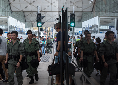 Riot policemen at the airport's departure hall. Riot police swarmed the Hong Kong International Airport in anticipation of a planned disruption by protesters. Police questioned and searched certain individuals upon their arrival at the airport.