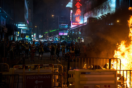 Protesters retreat from the Mong Kok police station after setting a street on fire  during the demonstration Protesters occupied streets outside of Prince Edward MTR station while also continuing to pay respects at one of the station exit. Riot police and police special forces were deployed to conduct dispersal operations.