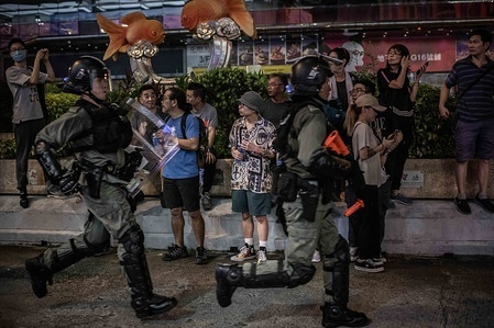 Residents of Mong Kok area observe a group of riot police chasing demonstrators on Nathan Road during the protests. After 14 weeks of protests, demonstrations have continued across Hong Kong despite the withdrawal by Chief Executive, Carrie Lam of a controversial extradition bill.  Protests keep taking the streets as demonstrators demands the city's government to attend to their demands, including an independent inquiry into police brutality, the retraction of the word 'riot' to describe the rallies, and the right for Hong Kong people to vote for their own leaders.