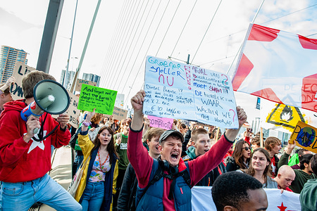 A protester shouts slogans while holding a placard during the demonstration. During the famous world harbour days of Rotterdam, a Climate demonstration was organized by several organizations to demand that the harbour takes its responsibility for the climate crisis. According to the organizations involved in the march, the harbour of Rotterdam is responsible for 1/5th of the total CO2 emissions in the Netherlands. There was a strong police presence where the demonstration was passing by close to the Harbour Festival.