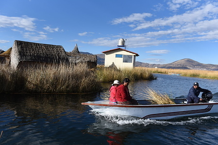 Uro family on board a motor boat sailing among the totora reed in Titicaca lake. The Uru or Uros are indigenous people of Peru and Bolivia, who live on an approximate hundred floating islands, made of Totora reed, in Titicaca Lake near Puno.  There are about 2.000 of them. The larger islands house 10 families while the small ones can be of only 30 metres wide hold 2 or 3 families.