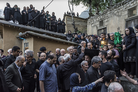 """People collect money during the ceremony. """"Tasht gardani"""" is a religious ceremony during Muharram in Masuleh. At the event, the Masuleh people move a ''tasht'' around the city to raise money which is spent on the mosque during Muharram. Masuleh is a historical city in northern Iran and in Gilan province."""
