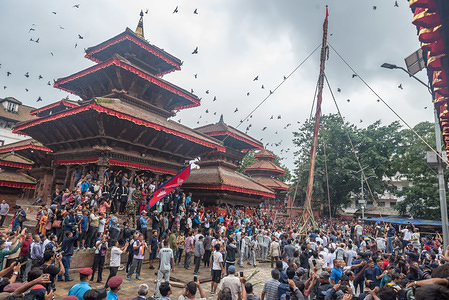 "People along with army help to erect the wooden pole during the ceremony. Indra Jatra most commonly known as ""Yenya"" in Nepal Bhasa which means celebration inside Kathmandu. Ya-Sin (Indradhoj Linga), a ceremonial wooden pole was erected in Hanumandhoka which marks the beginning of eight-day festival of Indra Jatra."