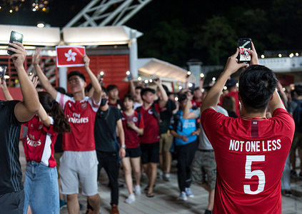 A protester wears an anti-extradition themed jersey referring to protesters '5 Demands' as others form a human chain during the halftime intermission. Hong Kong fans cheered for their team while also chanting various anti-extradition slogans. Protesters formed a human chain during the halftime intermission in hopes of drawing further attention to the unrest in Hong Kong. (Final score: Iran 2:0 Hong Kong)