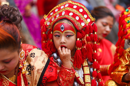 A young girl dressed as the Living Goddess Kumari reacts during the rituals. Kumari puja is a tradition of worshipping young prepubescent girls as manifestations of the divine female energy. The ritual holds a strong religious significance in the Newar community that seeks divine blessings to save small girls from diseases and bad luck in the years to come.