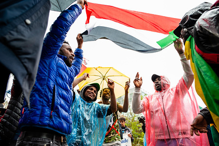 A group of Sudanese people dance below a Sudanese flag during the march. From September 6th to 11th, an international Sudanese march took place starting in London and ending in The Hague after stopping in France and Belgium. On September 11th, the march arrived in front of the International Criminal Court building, situated in The Hague. The march was held in solidarity with the Sudanese revolution and calls for the prosecution of military criminals in Sudan. The march was organized by the Sudanese Initiative Europe.