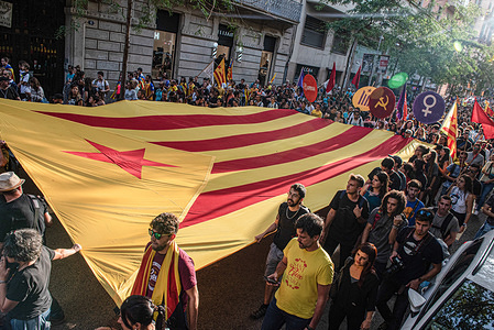 Protesters hold a large independence flag through the demonstration on the National Day of Catalonia, which has been organized by the Catalan National Assembly.