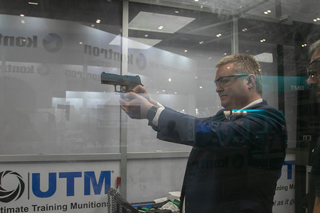 A delegate holds a handgun as he prepares to fire live ammunition rounds on the Ultimate Training Munitions demonstration stand during the last day of the DSEI arms fair at ExCel, the world's largest arms fair which is held biannually in London's Docklands.