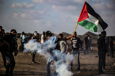 A Palestinian demonstrator returns a tear gas canister at Israeli security forces during an anti-Israel demonstration at the Israel-Gaza border fence in the southern Gaza Strip.