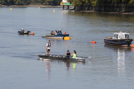 People enjoy rowing their boats at the River Thames on a warm and sunny day in London.