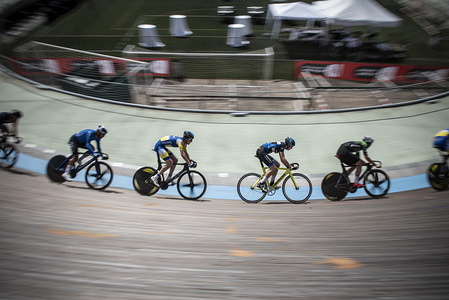 Several race participants seen at the curve of the cycling track during the International track cycling test at Velódromo de Horta. The 15th trophy of the city of Barcelona is an International track cycling test organized by the Catalan Cycling Federation with the support of the City Council of Barcelona, all the tests add points to the Olympic Games, and with a participation of nearly sixty cyclists from different countries.