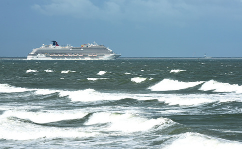 The Carnival Breeze cruise ship heads out to sea as rough surf generated by the Tropical Storm Humberto is seen as the storm moves north off the coast of Florida.