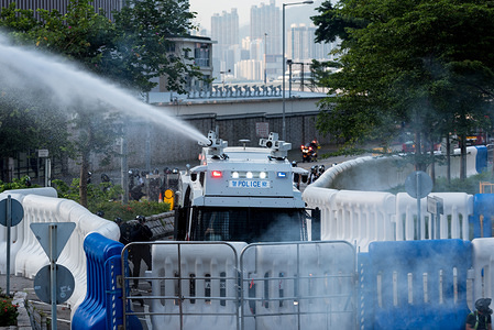 A riot control vehicle fires a liquid solution at protesters during the demonstration. Thousands of protesters marched through the streets on the 15th continuous week of unrest. While the demonstration began peacefully, protesters later faced off against police in front of government offices. Protesters threw bricks and petrol bombs while police attempted to keep the demonstrators at bay by firing dozens of tear gas rounds and blunt projectiles. Riot police eventually deployed vehicles equipped with water cannons and conducted a full dispersal operation. Protesters continue to fight for the remaining four demands after the extradition bill was formally withdrawn the previous week.