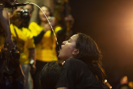 A Nepalese girl drinks alcohol poured from the mouth of Swet Bhairab during the Indra Jatra festival. Women and girls gather to drink holy alcohol poured from the mouth of Swet Bhairab as a blessing. The Indra Jatra is celebrated to honour Indra, god of rain and the king of gods.