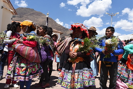 Relatives and friends of bride and groom wait outside church during the religious ceremony. Local bride and groom get married at the church of Peruvian village in the Sacred Valley of the Incas. Relatives and friends wear traditional costumes for the ceremony, which was held in native Quechua language.