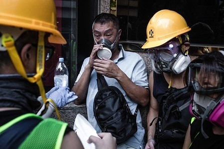 A man is being helped by the first aid crew and protesters after feeling dizzy with teargas during a pro-democracy march.