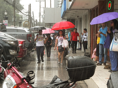 Commuters hold umbrellas during the downpour. The southwest monsoon, locally known as habagat, will bring scattered rains over Metro Manila, Zambales, Mimaropa, Calabarzon and West Visayas according to PAGASA Weather Specialist Gener Quitlong.