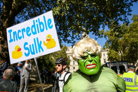 A man wearing a hulk face mask is seen outside UK Supreme Court in London with a placard, during the first day of three day appeal hearing in the multiple legal challenges brought by political activist and MPs against the British Prime Minister Boris Johnson's decision to prorogue Parliament ahead of the Queen's speech on 14 October.