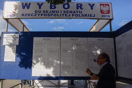 A man at an information stand for the upcoming Poland's Parliamentary elections at the Main Square. With Poland's general election less than a month away, the country's ruling Law and Justice party (PiS) has announced another package of proposals promising changes on social spending, journalism laws and the prosecution of parliamentarians.