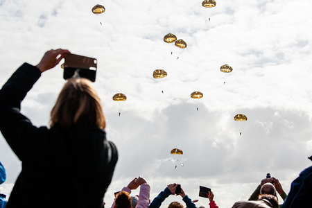 A group of people are seen taking photos of the paratroopers in the sky. In September it's exactly 75 years ago that paratroopers from the 82nd Airborne Division landed in Groesbeek as part of the Operation Market Garden. More than 1,000 paratroopers are expected to recreate the landing in Groesbeek. For these jumps, the 'Parachute Group Holland' hired two original C-47 Dakotas from England. One of these Dakotas is called Drag 'em Out, made several flights during the Second World War at the invasion of Europe over France and Operation Market Garden in the Netherlands. In addition to the permanent members from The Netherlands, members from England, Poland, the Czech Republic, Canada, and the United States also participated.