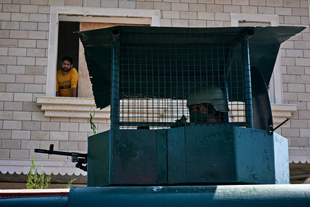 A paramilitary trooper keeps vigil as a resident looks out from window during the shutdown in Srinagar, Kashmir. Kashmir valley remained shut for the 45th consecutive day following the scrapping of Article 370 by the central government which grants special status to Jammu & Kashmir.